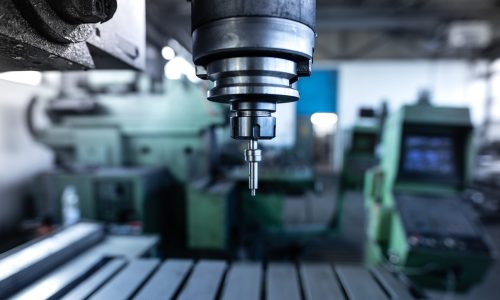 Industrial metal drill machine in metalworking workshop.