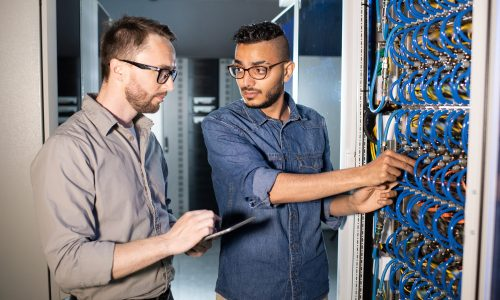 Serious pensive smart young multi-ethnic IT workers in glasses standing by cabinet of server and repairing server together
